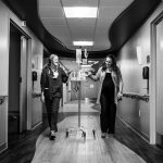 Woman in labor walking down hall with Madison Women's Health OBGYN providers