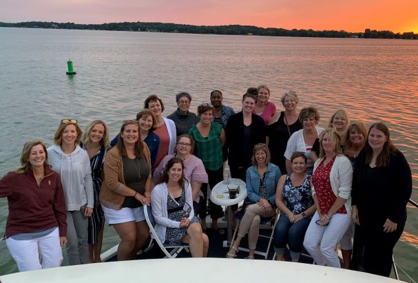 Madison Women's Health OBGYNs, female gynacologists and other staff standing by lake at sunset